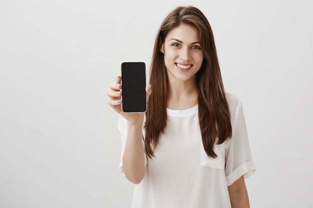 Mulher feliz e sorridente mostrando uma tela de celular, um aplicativo recomendado ou um site de compras