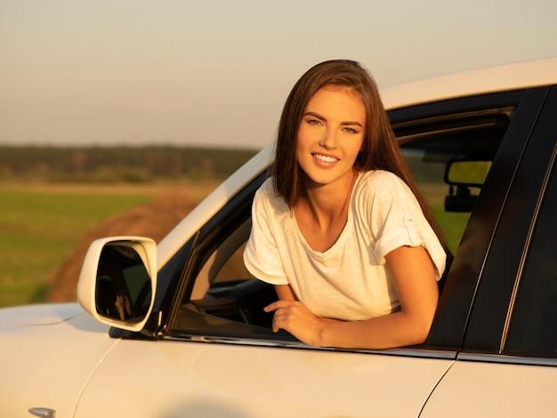 Mulher feliz e sorridente no carro, olhando pela janela.