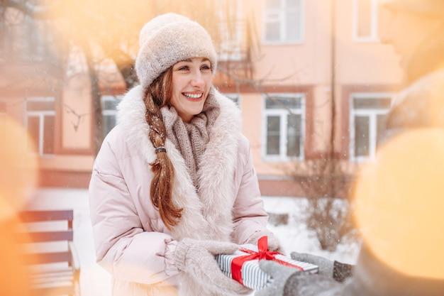 Mulher feliz e sorridente recebe um presente do namorado no dia dos namorados em um parque de inverno nevado. uma jovem fêmea recebe um presente ao ar livre em um dia frio de inverno. férias e conceito de presentes.