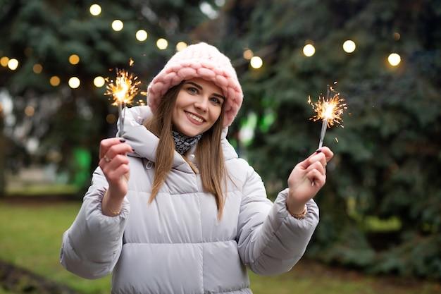 Mulher feliz e sorridente se divertindo com estrelinhas perto da árvore do ano novo