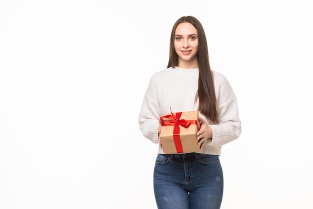 Mulher feliz e sorridente segurando uma pequena caixa de presente vermelha isolada na parede branca
