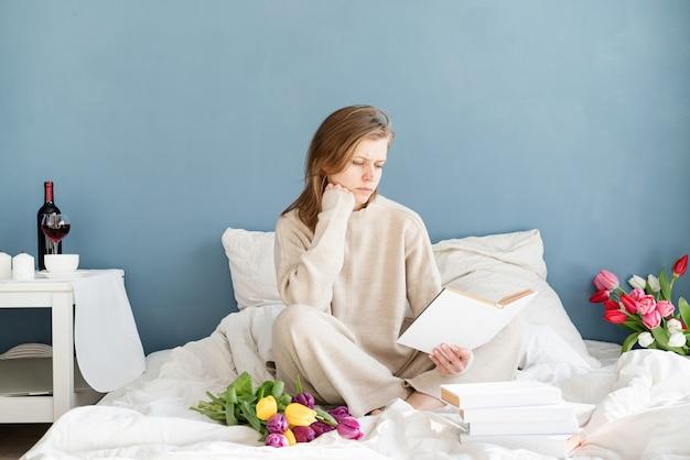 Mulher feliz e sorridente, sentada na cama de pijama, com prazer, curtindo flores e lendo um livro