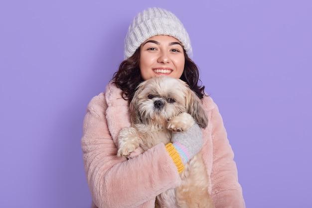 Mulher feliz e sorridente usando casaco de pele sintética e boné branco quente