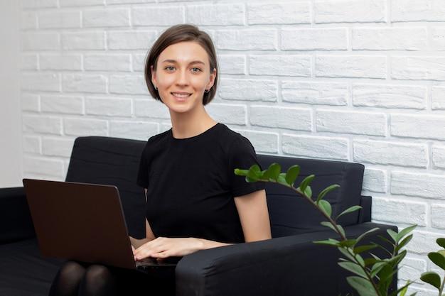 Mulher feliz e sorridente usando um laptop do escritório, sentada no sofá