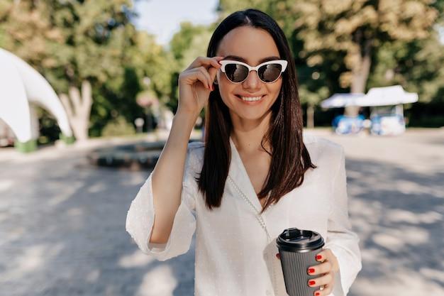 Mulher feliz e sorridente, vestindo camisa branca e óculos brancos, bebendo café do lado de fora em um bom dia de sol no parque da cidade