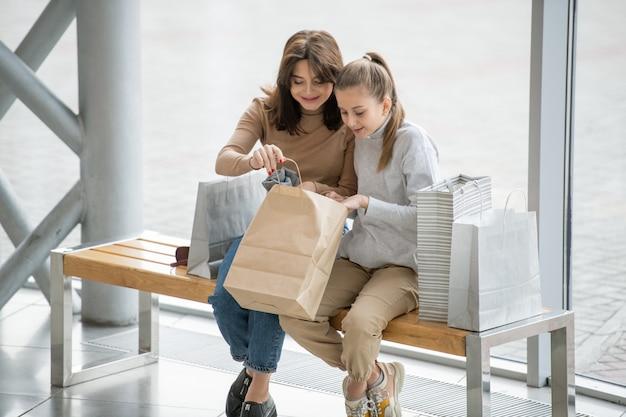 Mulher feliz e sua filha abrindo a bolsa de papel e olhando o que compraram como presente para o pai ou amigo