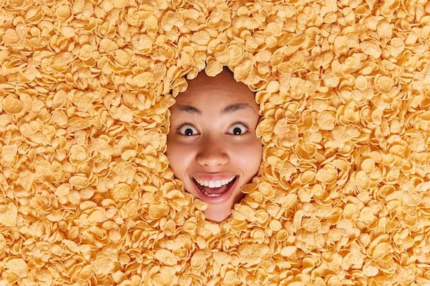 Mulher feliz e surpresa com um sorriso largo, não consegue acreditar que seus olhos enterrados em flocos de milho secos estão em volta de cereais e reage a algo emocionante indo tomar café da manhã