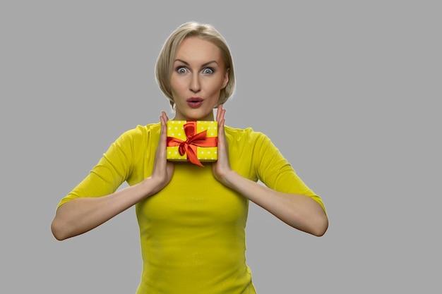 Mulher feliz e surpresa segurando a caixa de presente. mulher jovem animada segurando uma pequena caixa de presente com as duas mãos contra um fundo cinza. oferta especial de férias.
