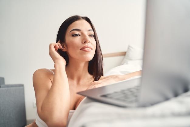 Mulher feliz e terna sentada no chão com o gadget e olhando para a tela do quarto dela