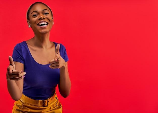 Mulher feliz em brincos em uma camiseta azul em uma saia amarela aponta