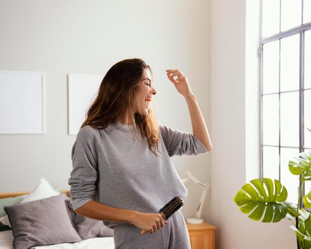 Mulher feliz em casa cantando enquanto segura a escova de cabelo
