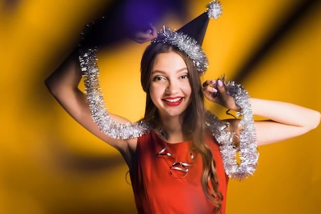 Mulher feliz em chapéu festivo em fundo amarelo