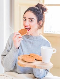 Mulher feliz em cinza comendo biscoitos