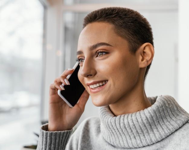 Mulher feliz em close falando ao telefone