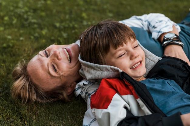 Mulher feliz em close-up e criança na grama