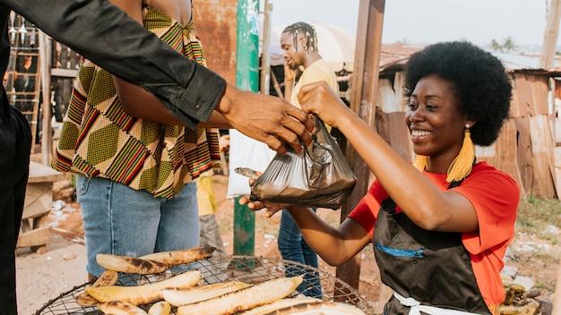 Mulher feliz em close vendendo comida