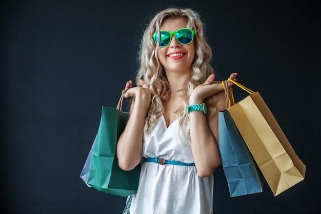 Mulher feliz em copos com sacos de compras