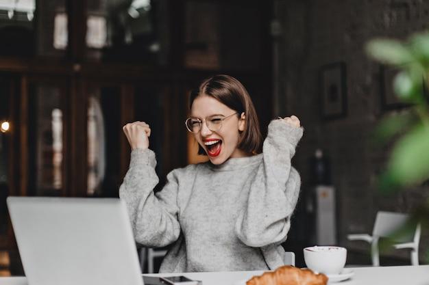 Mulher feliz em copos faz gesto vencedor e sinceramente se alegra. senhora com batom vermelho vestida de suéter cinza, olhando para o laptop.