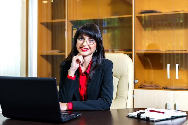 Mulher feliz em copos se senta em uma mesa no escritório