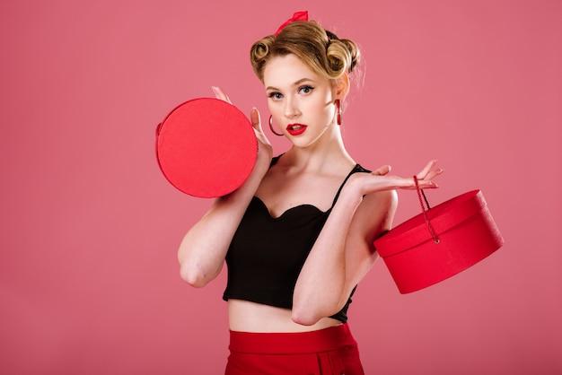 Mulher feliz em estilo retro, segurando sacolas vermelhas sobre o fundo rosa. retrato de pin-up