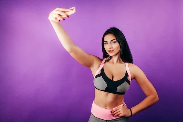 Mulher feliz em forma fazendo selfie em smartphone no estúdio