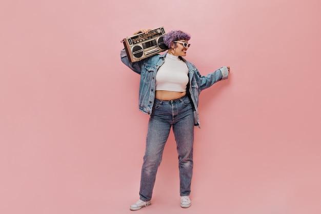 Mulher feliz em jaqueta jeans larga e calças justas, posando em rosa. mulher elegante em óculos de sol brancos segura o gravador.