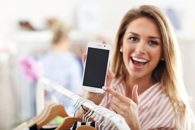 Mulher feliz em loja de roupas segurando smartphone