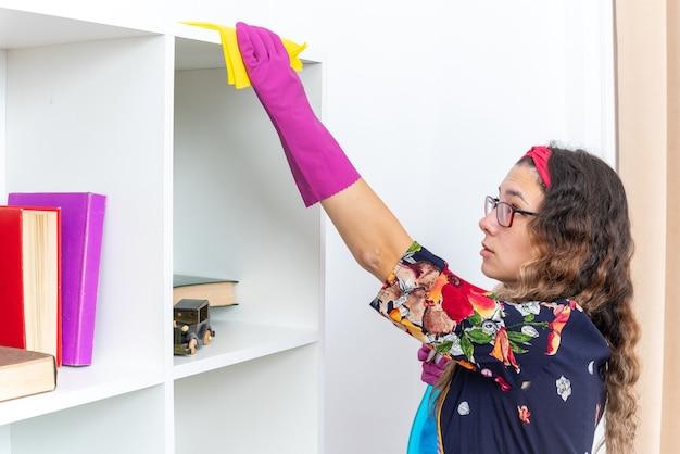 Mulher feliz em luvas de borracha, limpando prateleiras brancas com pano amarelo usando spray de limpeza em casa na luz da sala de estar
