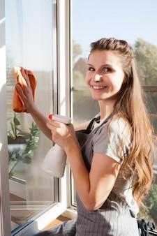 Mulher feliz em luvas de limpeza de janela com pano e limpador spray em casa