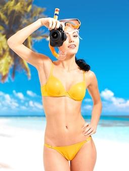 Mulher feliz em maiô amarelo com uma câmera digital tirando fotos na praia