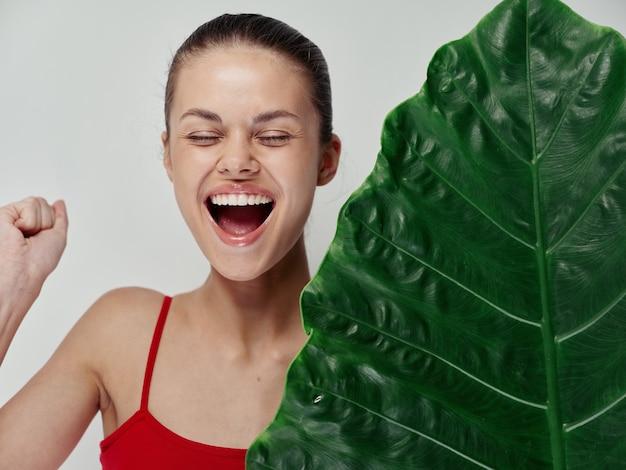 Mulher feliz em maiô vermelho rindo com a boca bem aberta e modelo de pele limpa de palmeira de folhas verdes