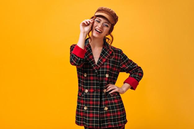 Mulher feliz em óculos, boné e jaqueta xadrez sorrindo na parede laranja