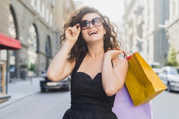 Mulher feliz em óculos de sol com sacos de compras