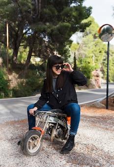 Mulher feliz em óculos de sol sentado na moto mini