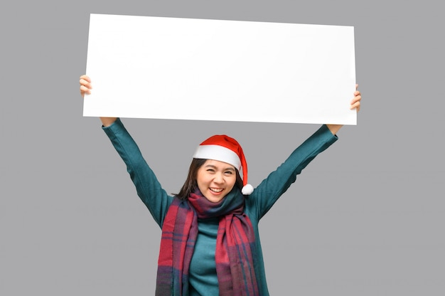 Mulher feliz em pano de tema de natal com chapéu de papai noel, apresentando faixa em branco