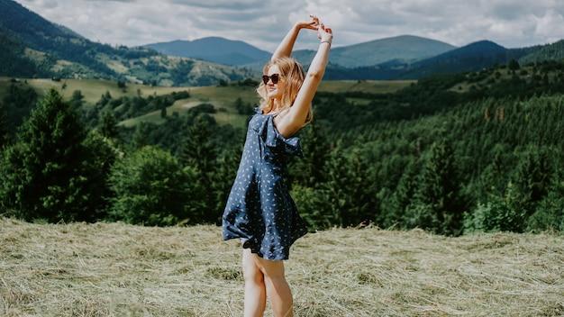 Mulher feliz em pé no topo da montanha