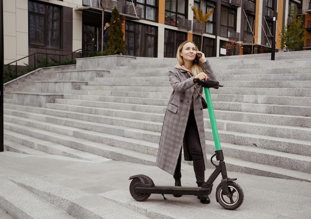 Mulher feliz em pé perto de scooter elétrica, olhando para o céu e falando ao telefone com um amigo. mulher jovem com casaco confortável feliz porque existe a oportunidade de alugar um veículo elétrico.