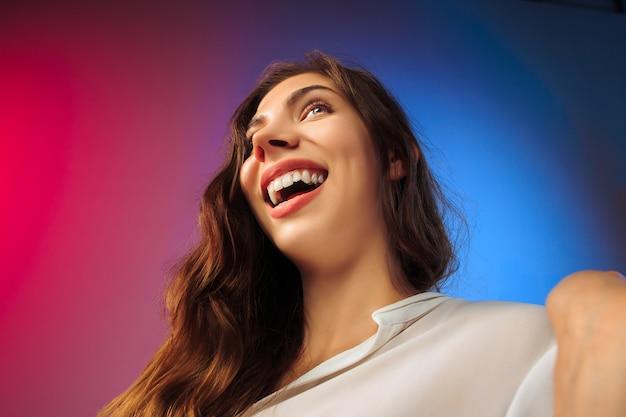 Mulher feliz em pé, sorrindo no fundo colorido do estúdio. belo retrato feminino de meio corpo. jovem satisfazer a mulher.