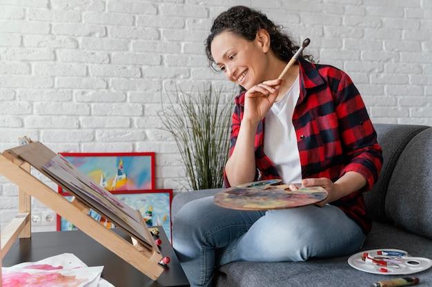Mulher feliz em plano médio pintando