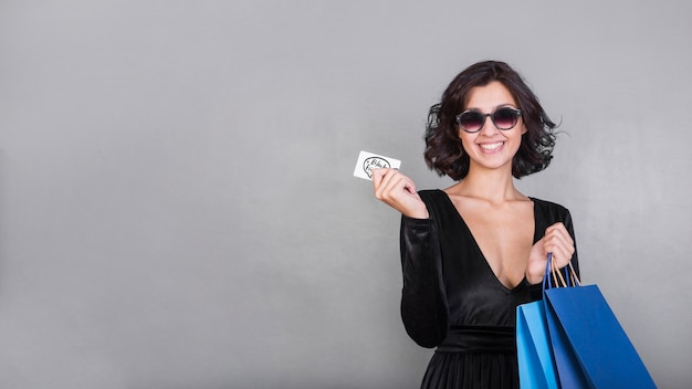 Mulher feliz em preto com cartão de crédito