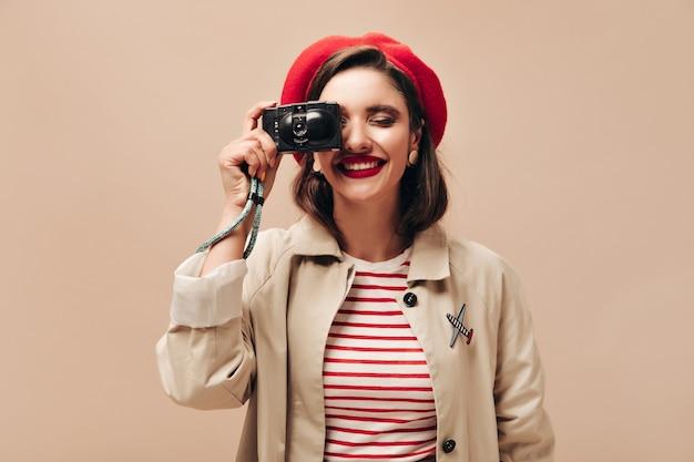 Mulher feliz em roupa bege segura uma câmera preta. jovem alegre de suéter listrado e casaco leve faz foto em pano de fundo isolado.