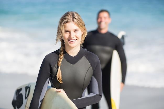 Mulher feliz em roupa de mergulho segurando uma prancha de surf na praia