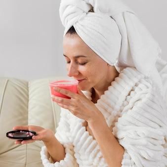 Mulher feliz em roupão de banho cheirando creme