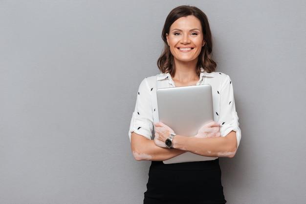 Mulher feliz em roupas de negócios, abraçando o computador portátil e olhando para a câmera em cinza