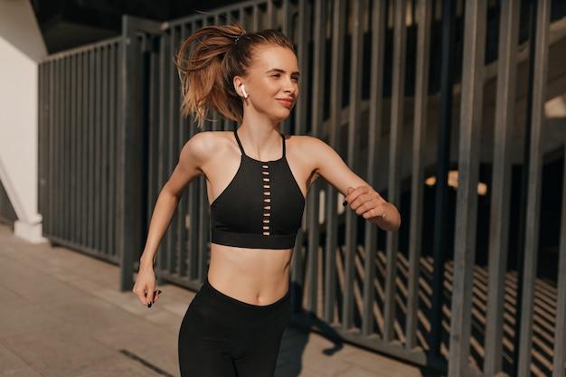 Mulher feliz em roupas esportivas correndo com fones de ouvido em um dia ensolarado na praça do esporte