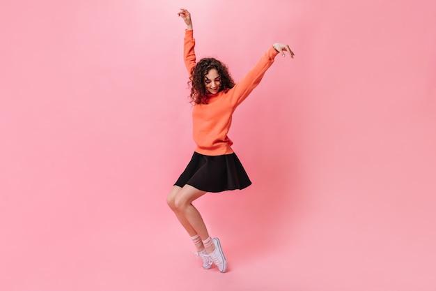 Mulher feliz em saia preta e suéter posando em fundo rosa