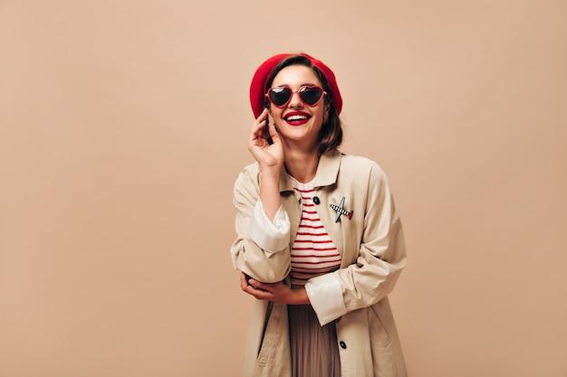 Mulher feliz em sorrisos de óculos escuros, chapéu e trincheira em fundo isolado. senhora alegre de suéter listrado e casaco bege posando.
