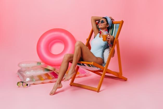 Mulher feliz em traje de banho deitada na espreguiçadeira