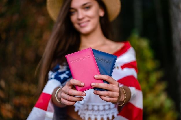 Mulher feliz em um chapéu de palha com uma bandeira americana e passaportes nas mãos dela