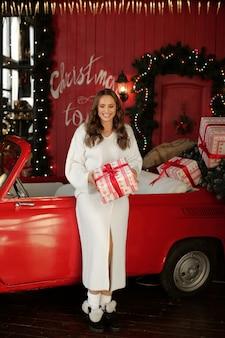 Mulher feliz em um vestido de malha branco com presente de natal ao lado de um carro retrô vermelho.
